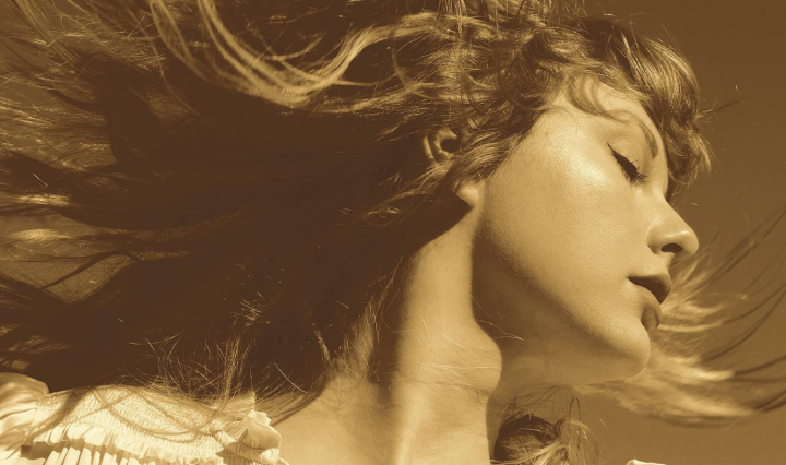 Taylor Swift looks to the right, her hair splaying out from the movement, her eyes are closed and she is wearing a frilly white blouse. The photo has a sepia style filter on it