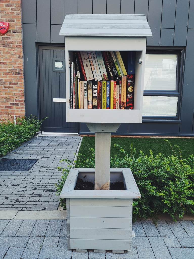 A box sits on top of a stick in a planter, it had a little slanted roof like a shed and inside there are two layers of books stacked