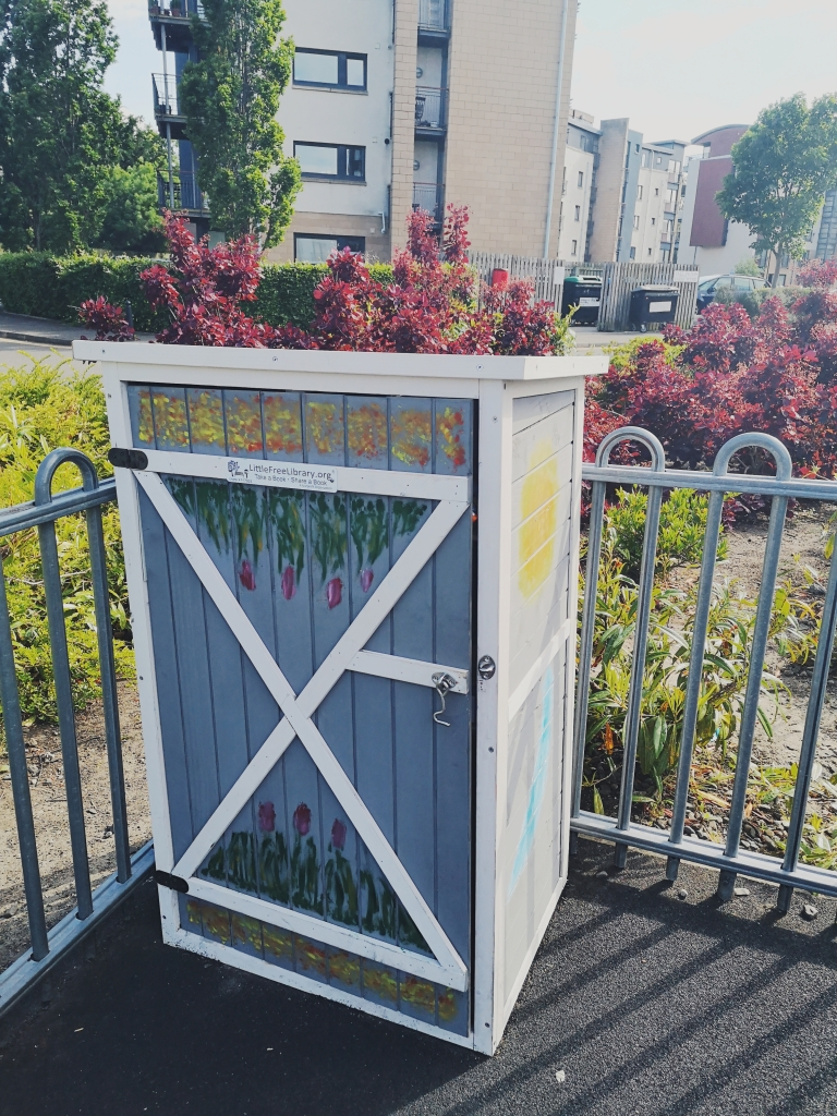A tall wooden box sits in the corner of a playground, it has flowers, leaves and the sun painted on it.