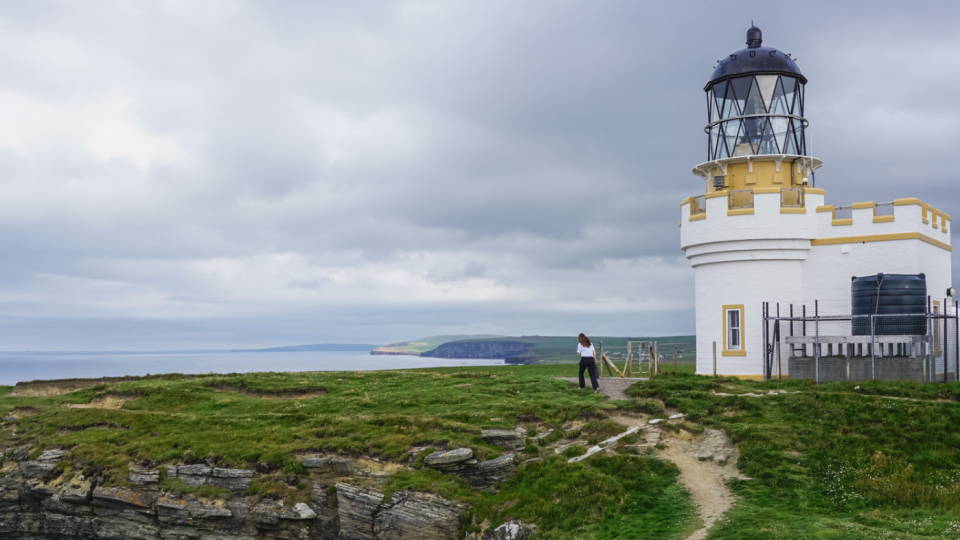 A white and yellow lighthouse on a grassy island