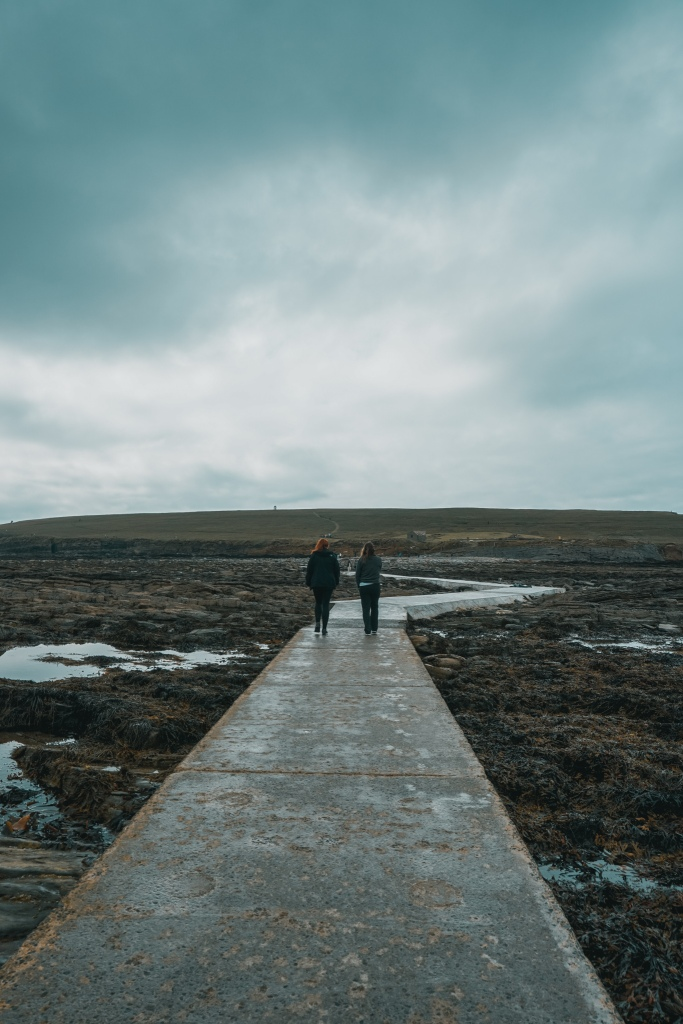 Two people can be seen walking over a stone path that is surrounded by seaweed