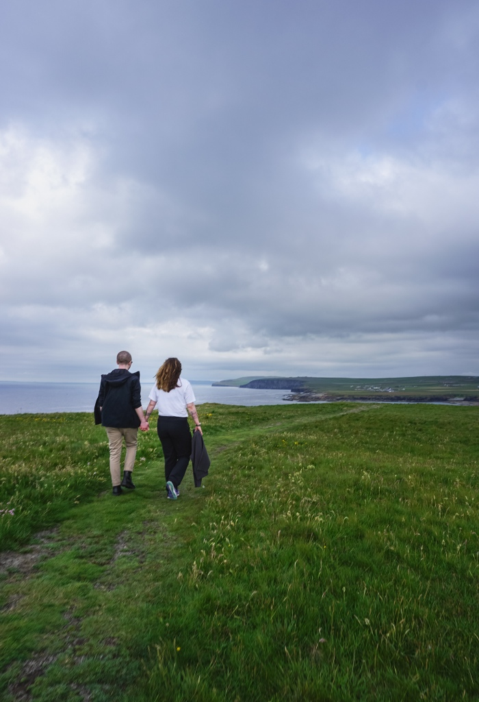 A man and woman hold hands as they walk over a grassy hill, we can see the sea and more coastline in the distance