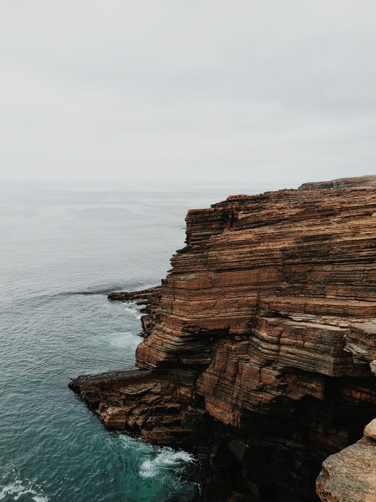 A layered brown cliffside poking out into the sea