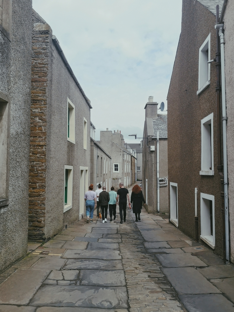 Six people are walking down a wee lane surrounded by little grey houses