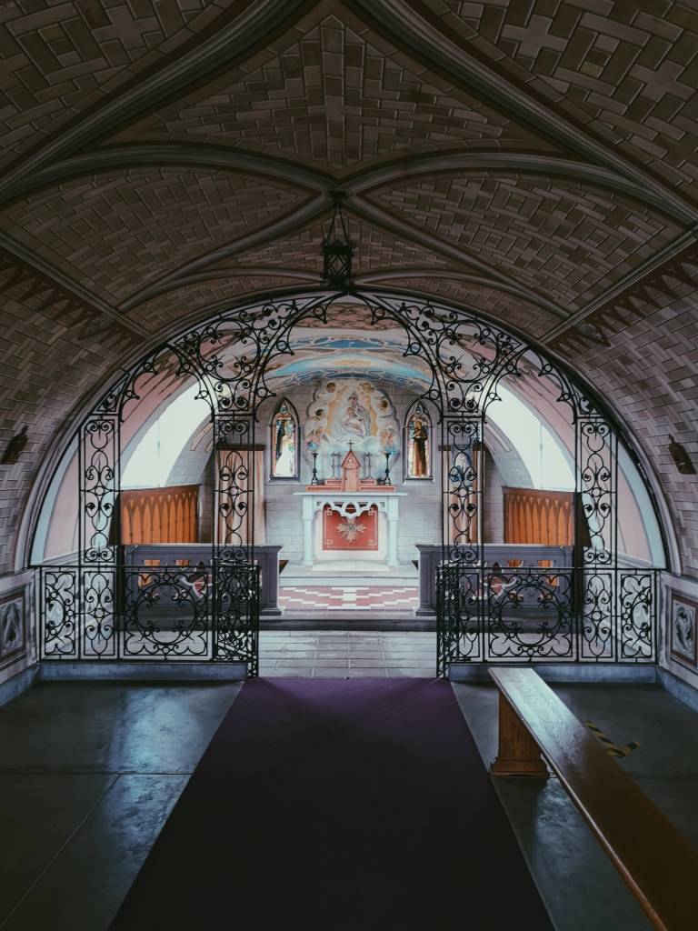 A room with a rounded ceiling there is wrought iron making an archway which leads to an altar