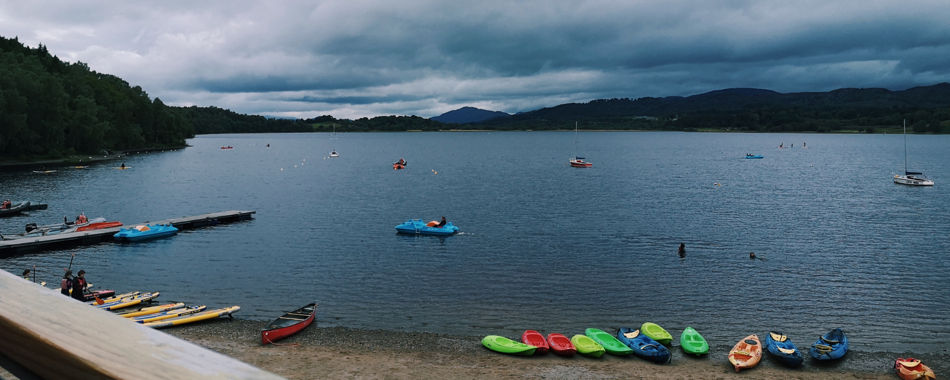 A large loch stretches to the distance, there are various kayaks, boats and paddle boards on the shore and in the water