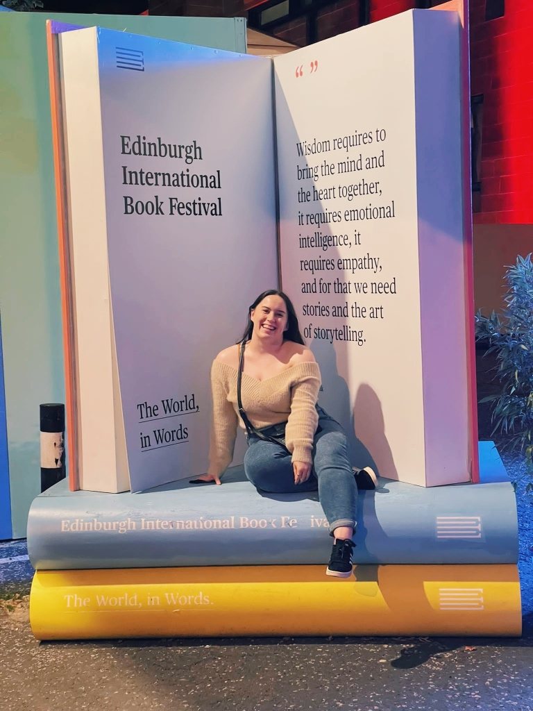 A young woman sits on a huge pile of books, they are large props and behind her one stands up, it has a quote about the wisdom of reading and says Edinburgh International Book Festival. The woman, Katie, wears jeans, a beige off the shoulder jumper and has long dark hair