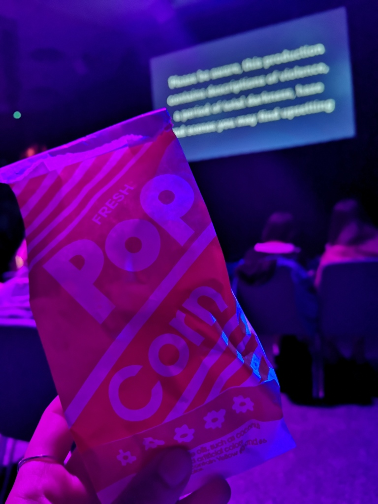 A small red and white bag that says pop corn on it, in the background blurred are some seats in front and a projector screen