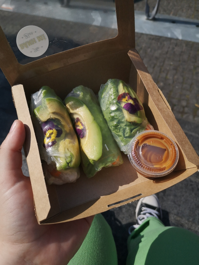 In a small cardboard box are three summer rolls and a tub of dipping sauce, through the rice paper we can see vegetables, avocado slices and some edible flowers