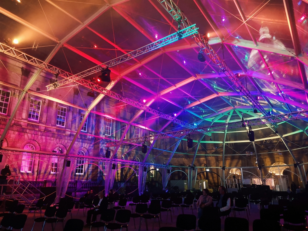 A large arched structure in a courtyard of old buildings, the big tent is transparent and glowing with various coloured lights